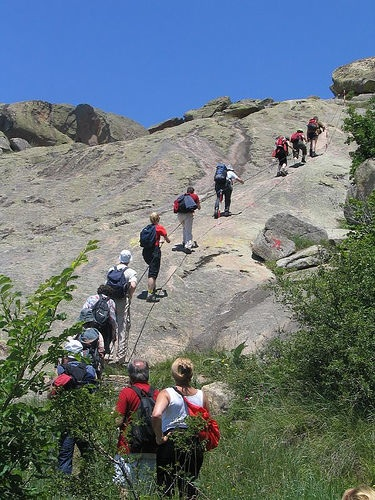 A group roped together climbing up the mountain
